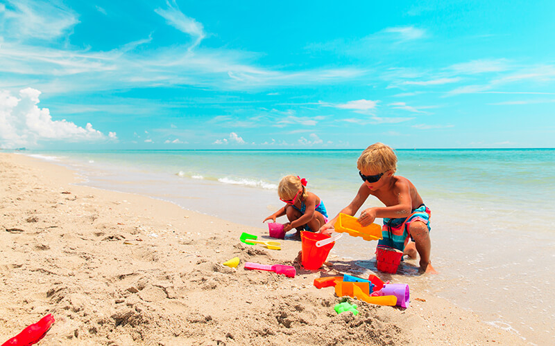 kids play with sand on summer tropical beach